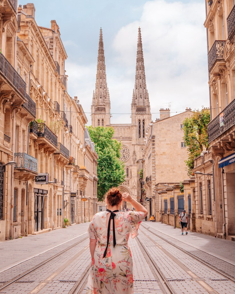 Woman with her back to the camera looking at Bordeaux cathedral from the Gambetta tram stop