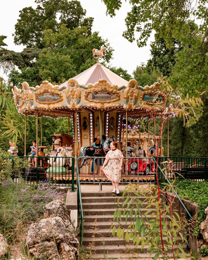 Woman looking at the carousel in the Jardin Public in Bordeaux which is a must see place to put on your Bordeaux itinerary