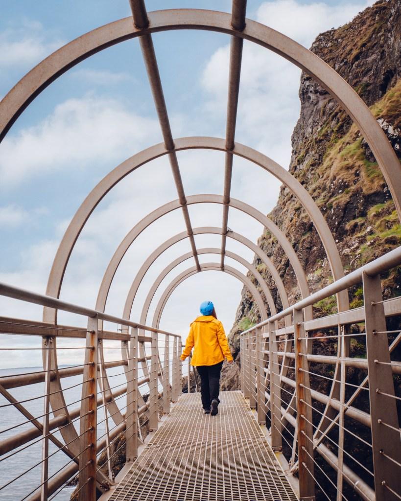 Woman in a yellow raincaot walking The Gobbins Cliff walk in Antrim Northern Ireland