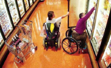 An image of persons in wheelchairs reaching for items at a store.