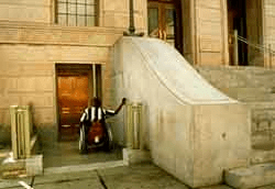 A photo of a presumably old stone building with a long steep stairs in front of the entry door. The man in a wheelchair is using an alternative door located at a lower level. It also shows that there is a door bell or automatic door opener that the man uses to open the door.
