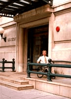 A photo depicting an entry/exit part of a presumably old stone building, pink in color with two steps in front of the door. A young white man in a wheelchair is leaving the building and using a ramp attached to the building.