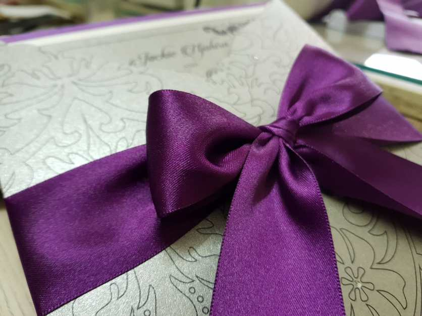 Luxurious purple ribbon on silver pocket invite
