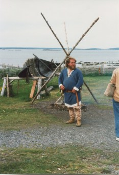 One of the costumed guides at L'Anse Aux Meadows by a fire and small boat. (Allan Lynch Photo)