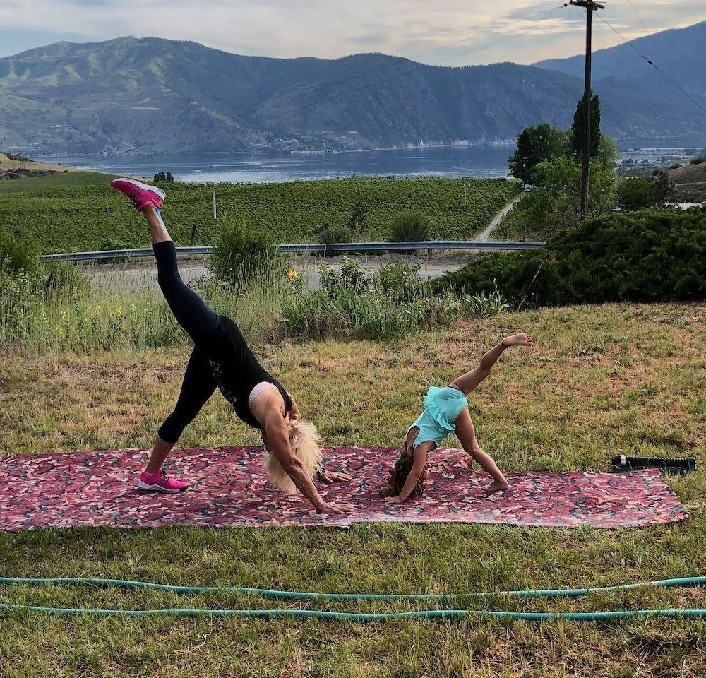Lady and child doing yoga in grass