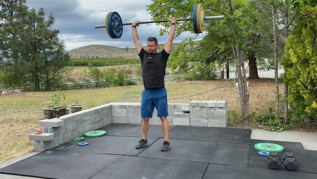 Joe Bauer doing barbell clean and jerks outside in Chelan