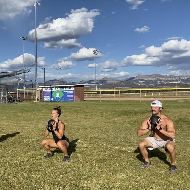 Emily and Joe doing goblet squats in the park. Goblet squats are great for workout newbies!