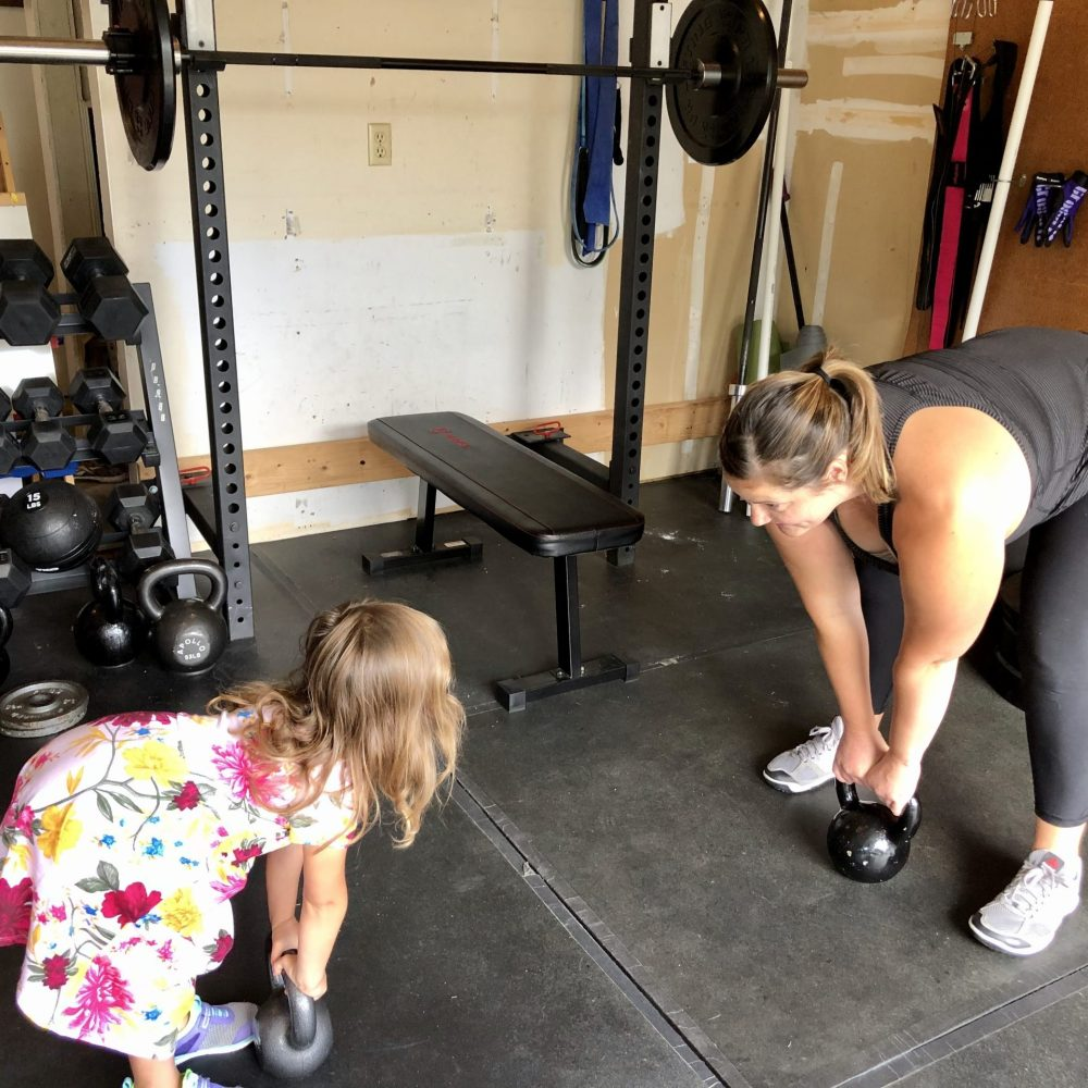 Mother and daughter working out with kettlebell swings