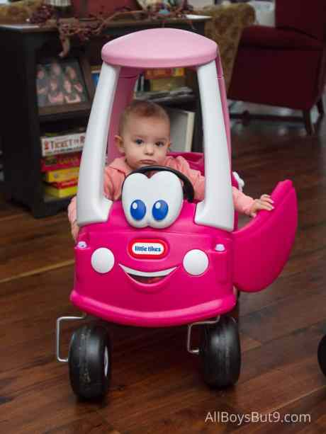 twin toddlers drive their toy cars.