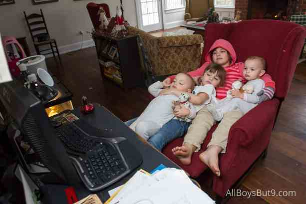 4 sisters snuggle up on an arm chair to enjoy a show.
