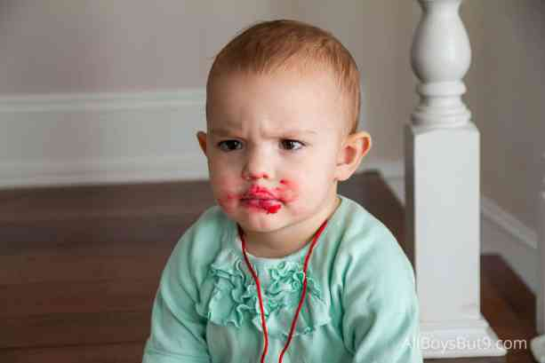toddler with first time self-applied lipstick