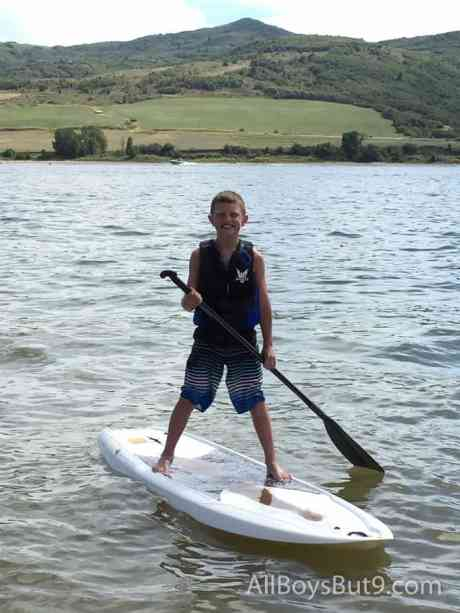 young boy on paddle board with a huge smile!