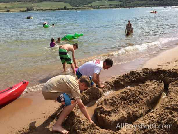 cousins dig a sand castle at the beach