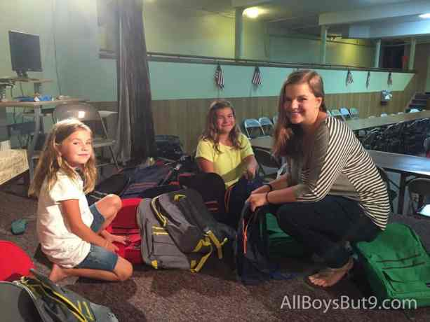 Kate, Esther, and Clara filling backpacks for school children who need them!