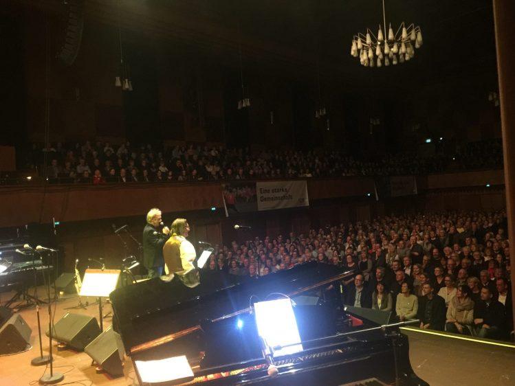 Richard Wester und Manfred Maurenbrecher auf der Bühne bei der Begrüßung des Publikums bei der Nacht der Lieder in Flensburg mit dem hamburger Bassisten David Alleckna.