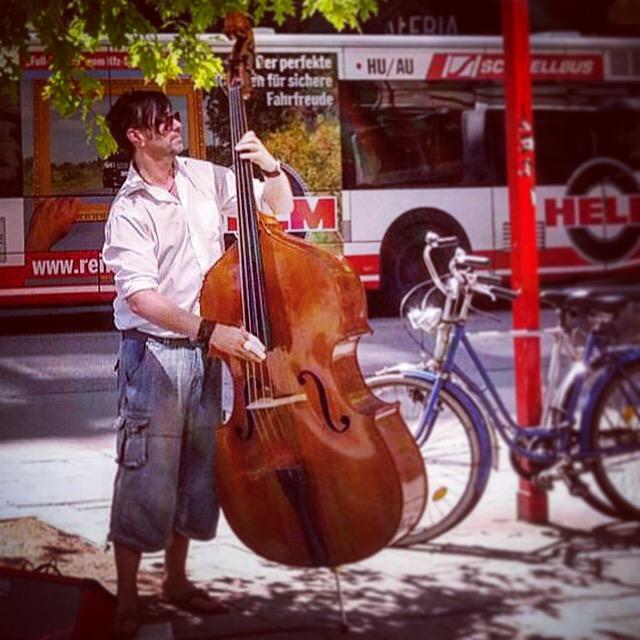 Der hamburger Bassist David Alleckna steht in der hamburger Mönkebergstraße mit seinem Kontrabass. Er promoted Musik des Musikers Wesley Collin George.