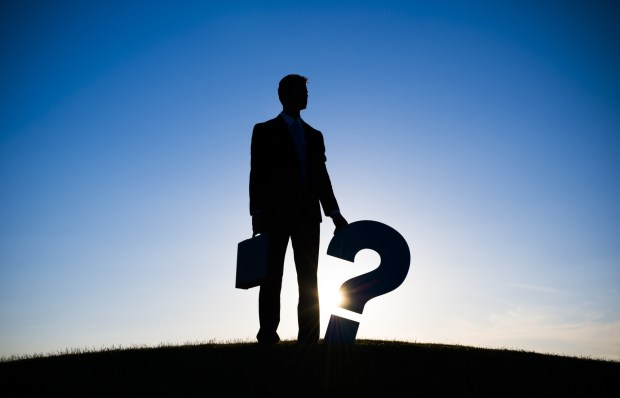Businessman holding Question mark on the hill