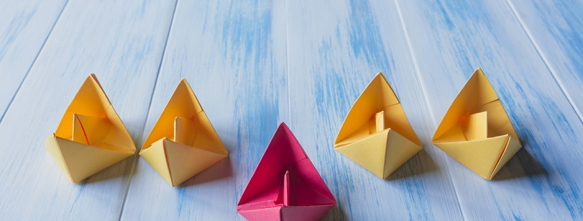Image of paper boats in a row with one standing in front of the rest