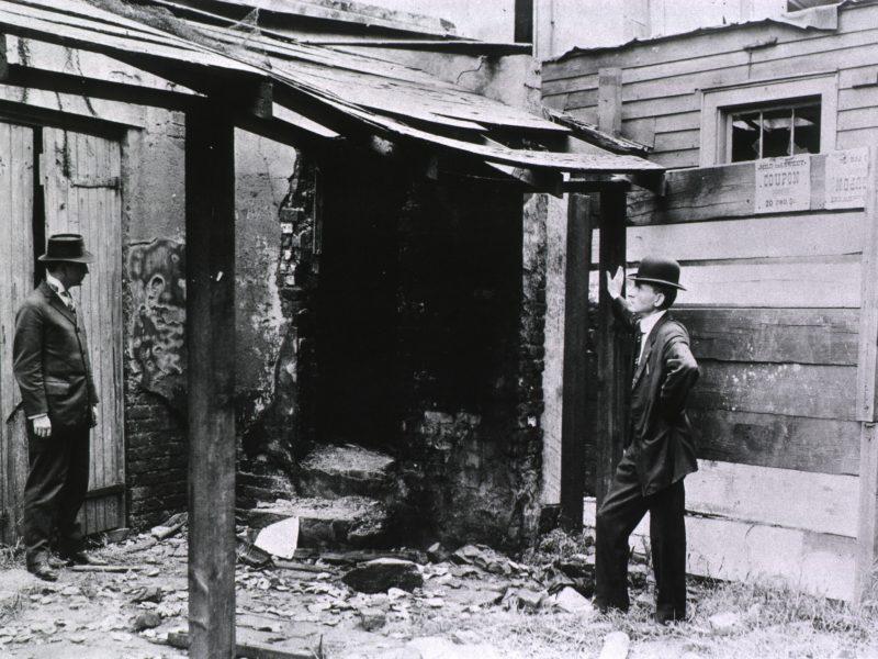 U.S. Public Health Service rat control, New Orleans, La. - Man sieht zwei Männer im Anzug vor einer für unser heutiges Empfinden ziemlich heruntergekommenen Hütte stehen, anscheinend im Gespräch.