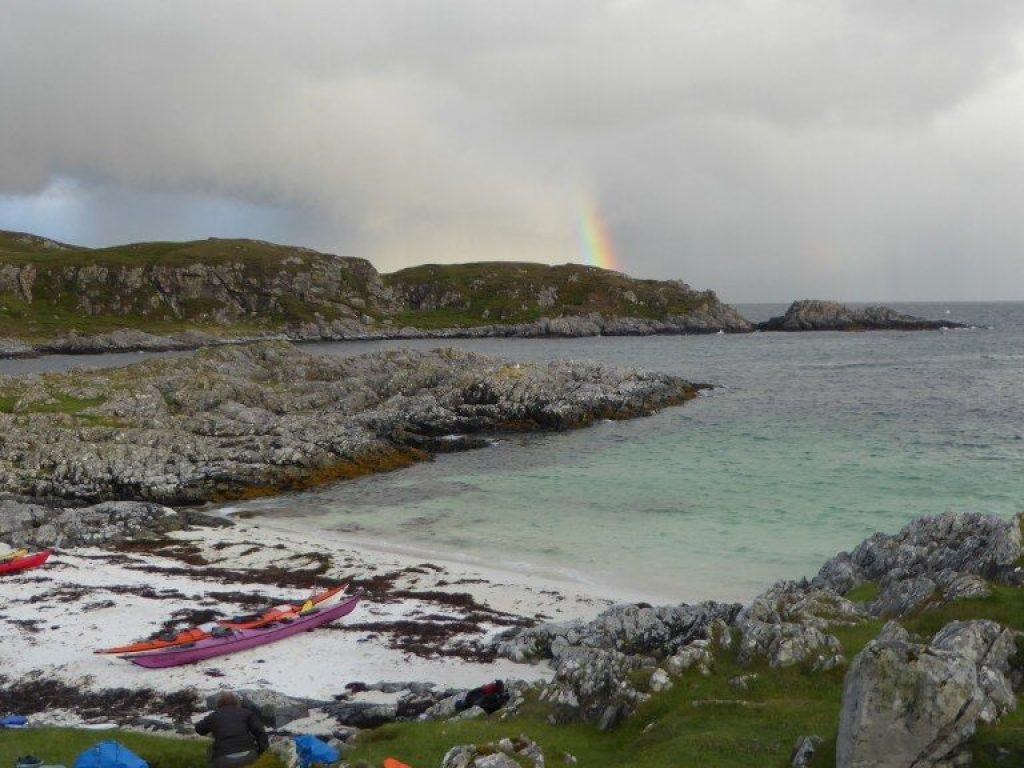 Popular Arisaig beach with tents and kayaks