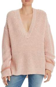 A woman wearing an oversized rose gold knit sweater.