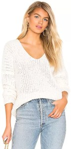 A blonde woman wearing a cropped white pullover sweater.