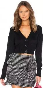 A woman wearing a cropped black cardigan sweater with a gingham print skirt.