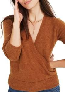 A posing woman wearing an orange faux wrap pullover sweater.