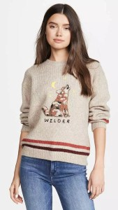 A woman wearing a graphic pullover sweater that features a howling wolf and the word 'wilder'.