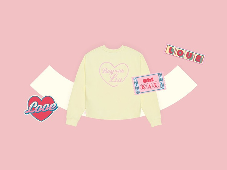 Boy With Luv official sweater and merch with a salmon pink background