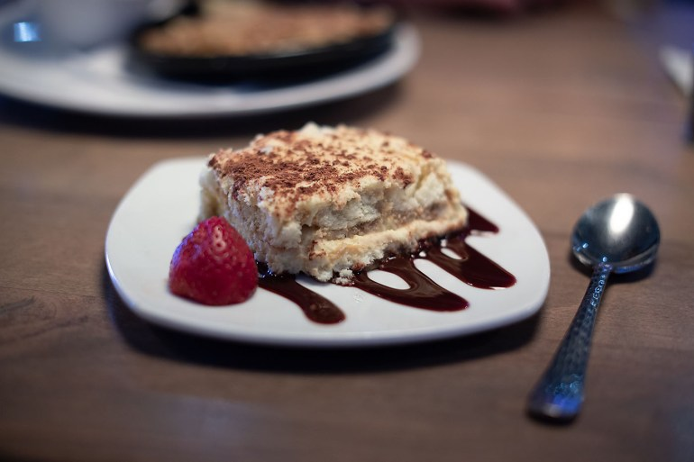 Tiramisu dessert on top of chocolate drizzle with strawberry