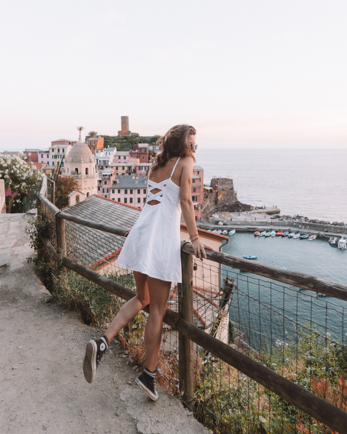 girl in white dress overlooking vernazza italy at sunset