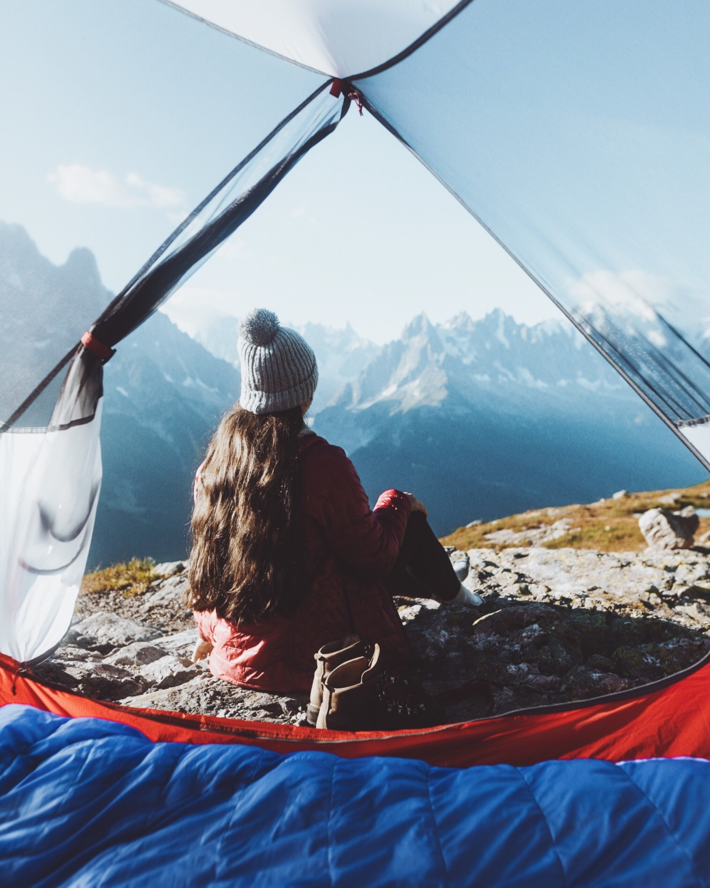 Girl sitting in the frame of a tent with sharp mountains in the distance