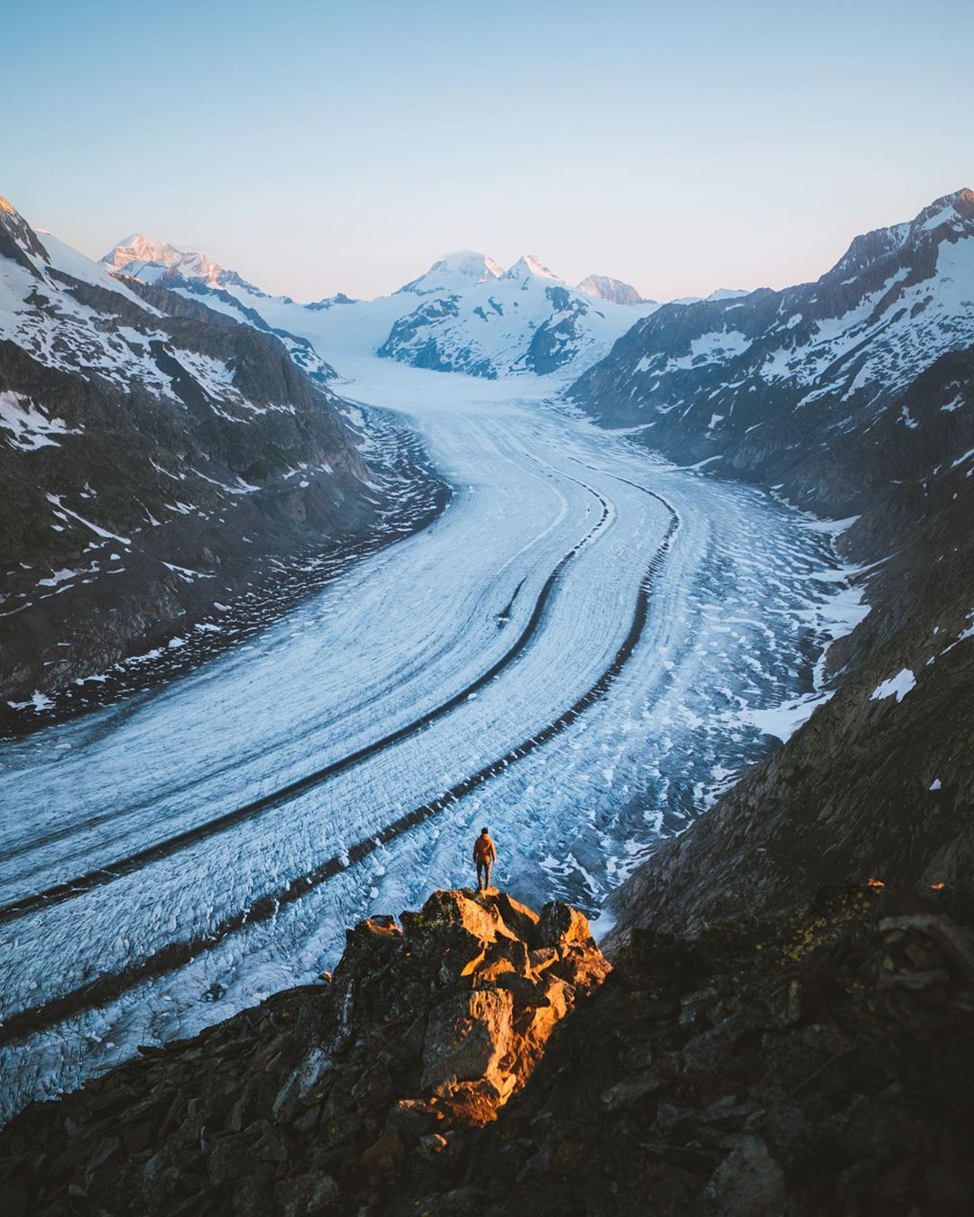 Aletsch glacier at sunrise with a man standing in front of it