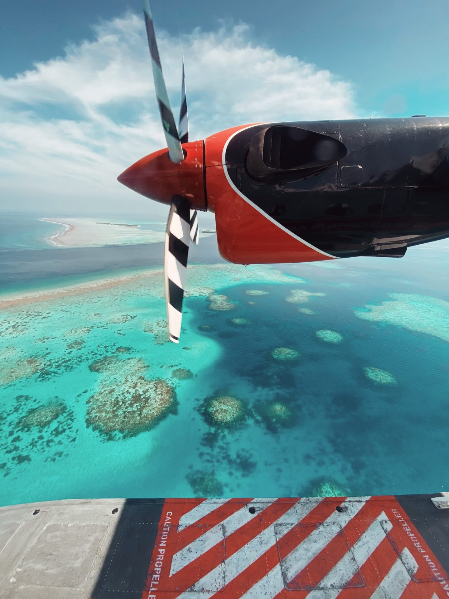 Window view from Maldives sea plane with turquoise blue water below
