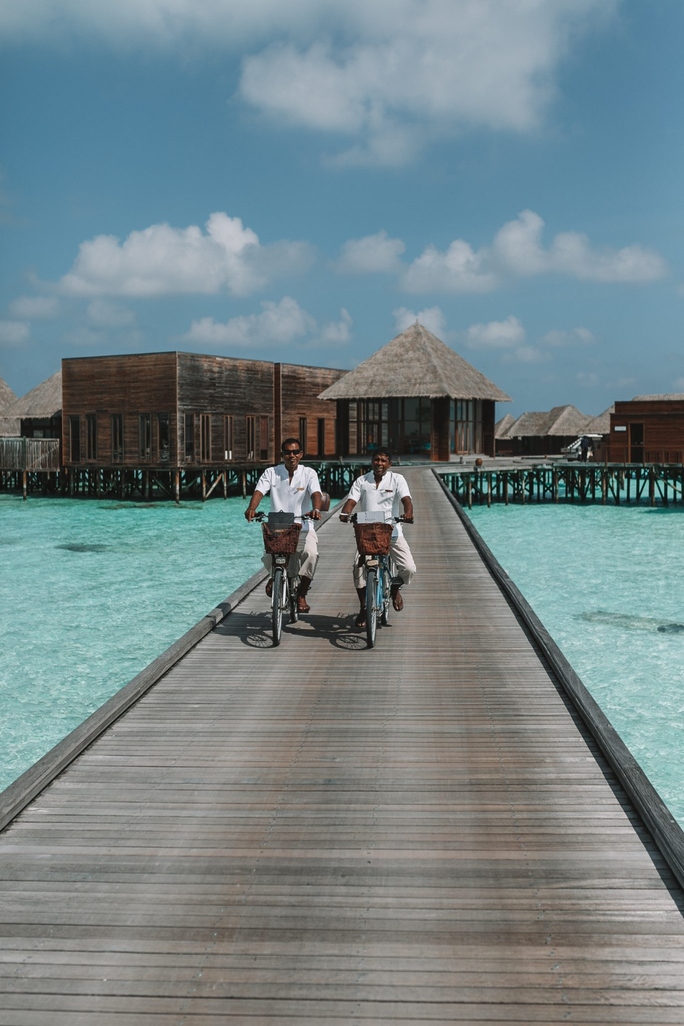 Two men riding bikes on a boardwalk in the Maldives