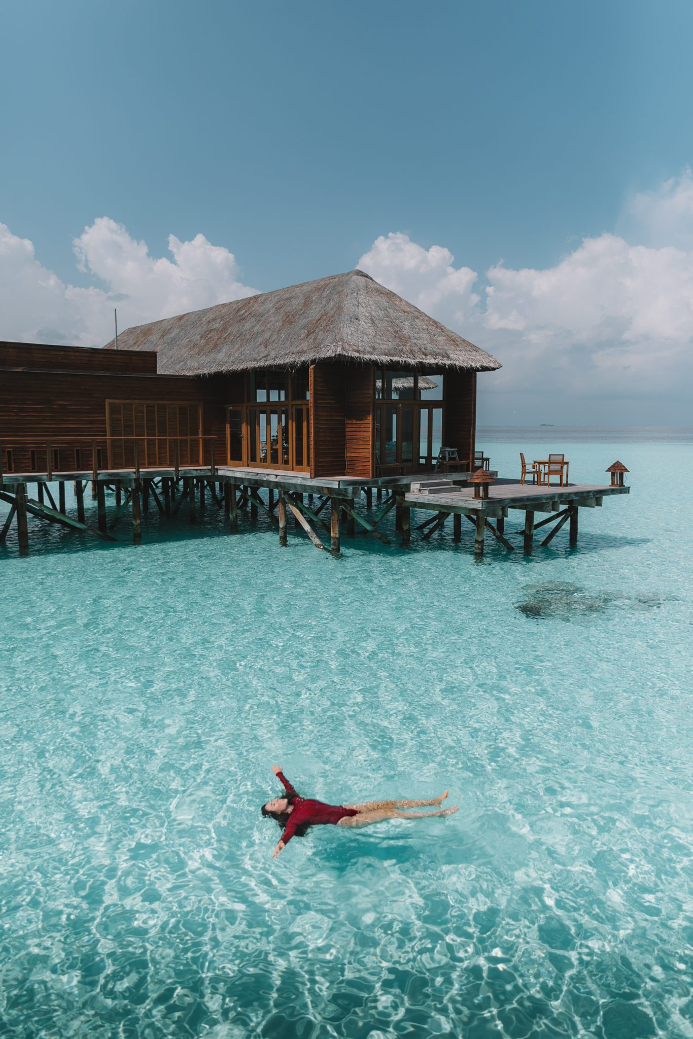 Girl floating in a red bathing suit in the ocean in the Maldives