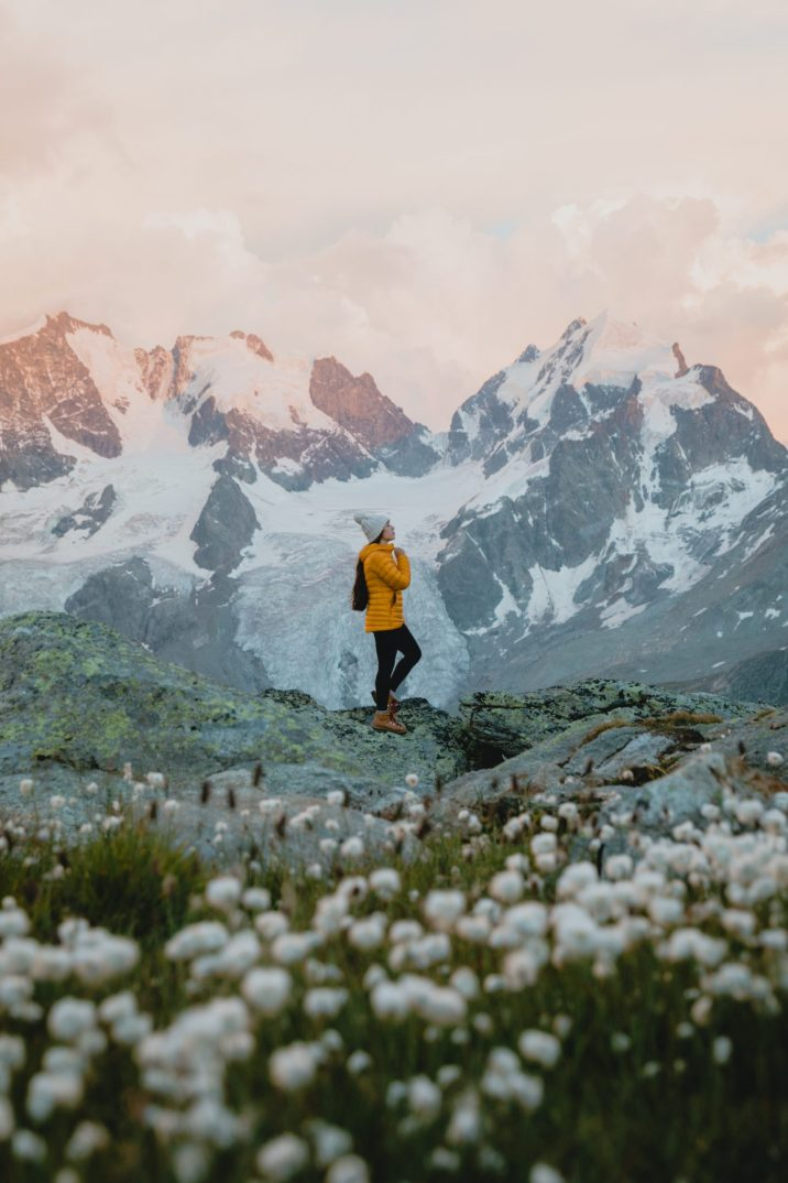 Girl with yellow jacket standing in front of glowing mountains at sunset
