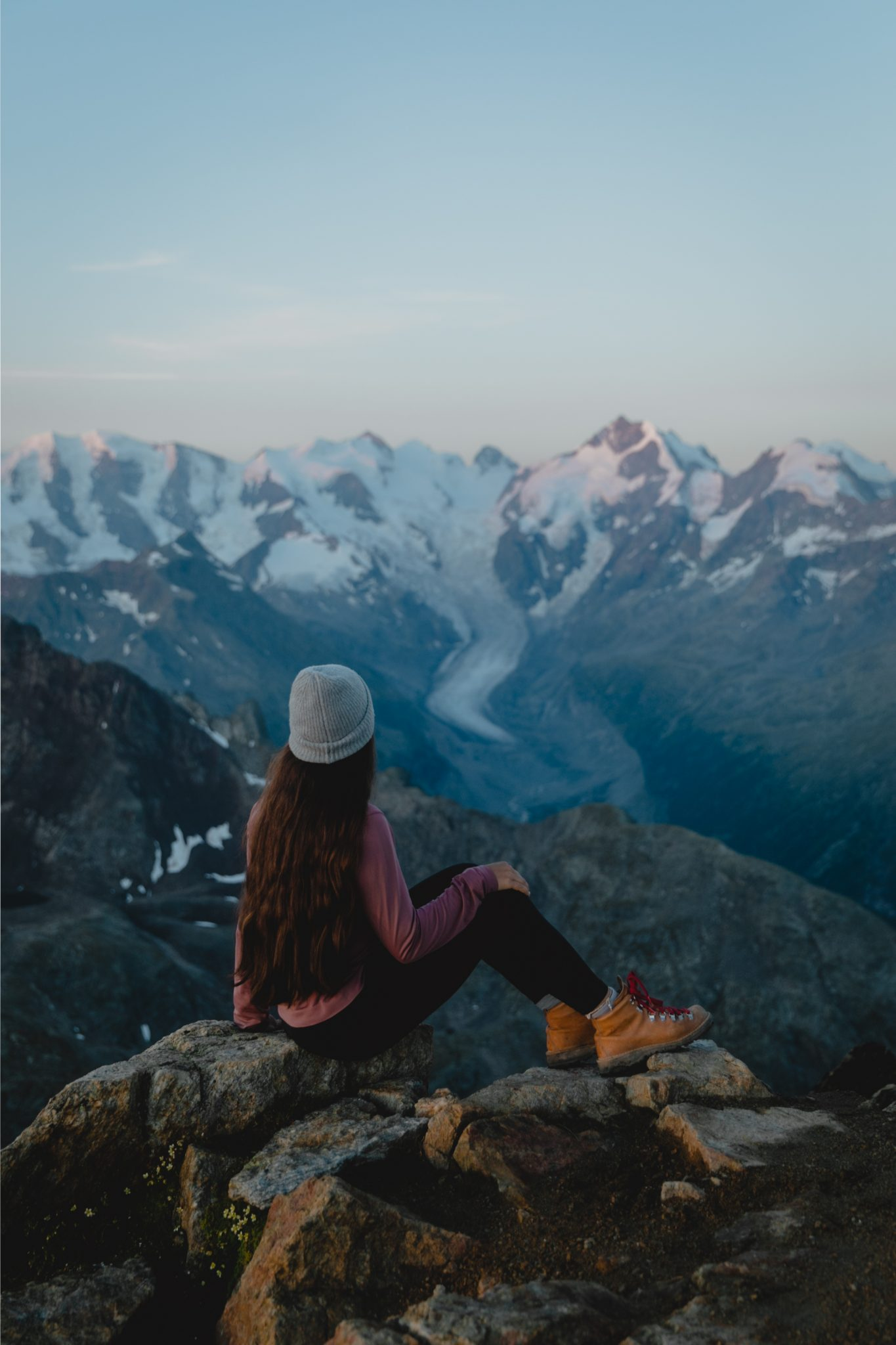 Girl sitting in front of a glacier at sunrise