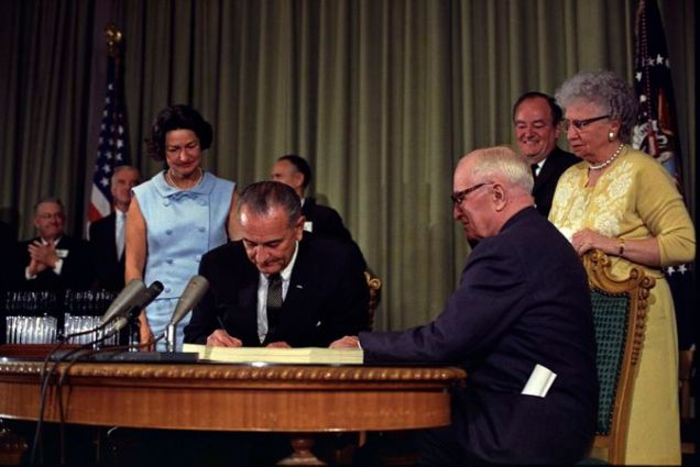 673px-Lyndon_Johnson_signing_Medicare_bill,_with_Harry_Truman,_July_30,_1965 (1)