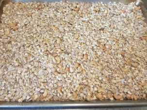Granola spread on a sheet pan and ready to bake.