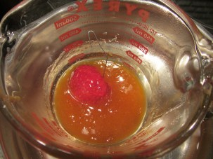Dipping a strawberry in apricot preserves/liqueur.