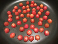 Halved grape tomatoes, searing in a hot pan.
