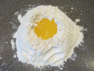 A well made in the flour, and some of the egg mixture added.