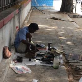 COIMBATURE. Shoe repairman sets up shop.