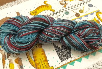 This yarn is an 85/15 blend of superwash Merino and Nylon which is perfect for sock yarn. So I split the yarn into long strips, spun them end-to-end, then chain-plied the singles to make self-striping sock yarn.