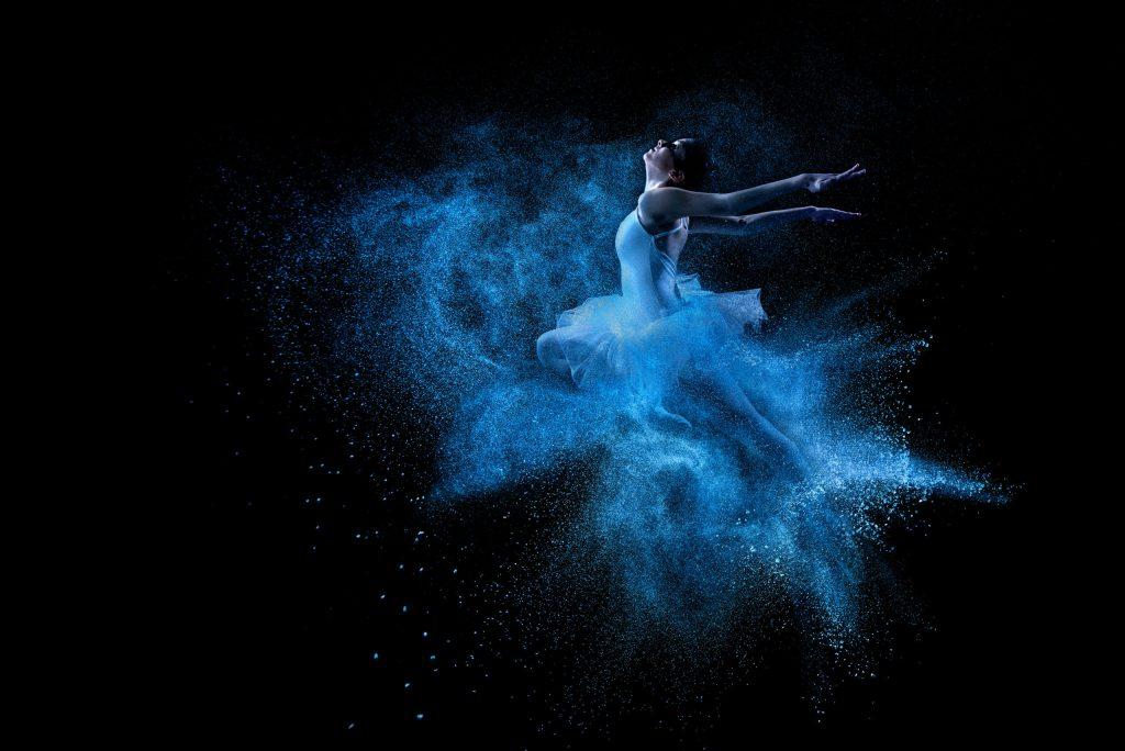 Eine Tänzerin springt in einer Wolke aus blauen Farbpartikeln und sieht nach oben.
