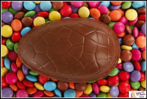 Large easter egg laying on top of smarties
