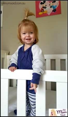 toddler standing in cot wearing The Sleepy Company X-TEND Sleepsuit
