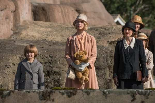 Margot standing with Christopher Robin holding teddy bear